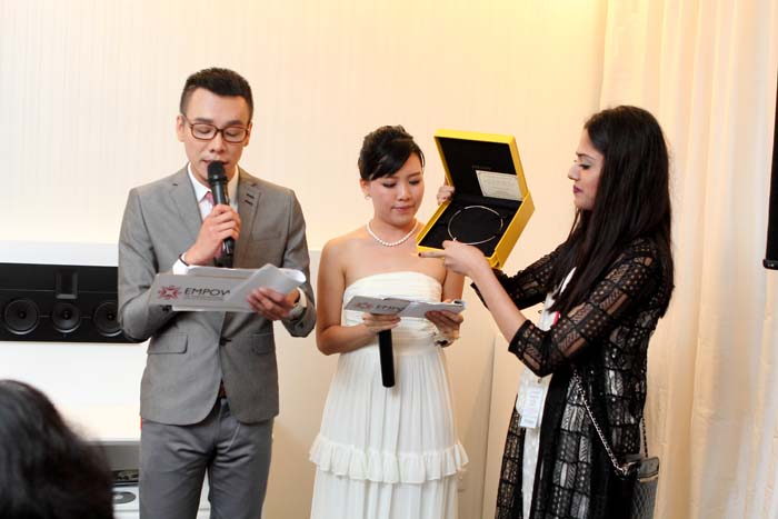 The MCs for 'Be an Angel with Tan Sri Michelle Yeoh' and a volunteer showcasing the auction