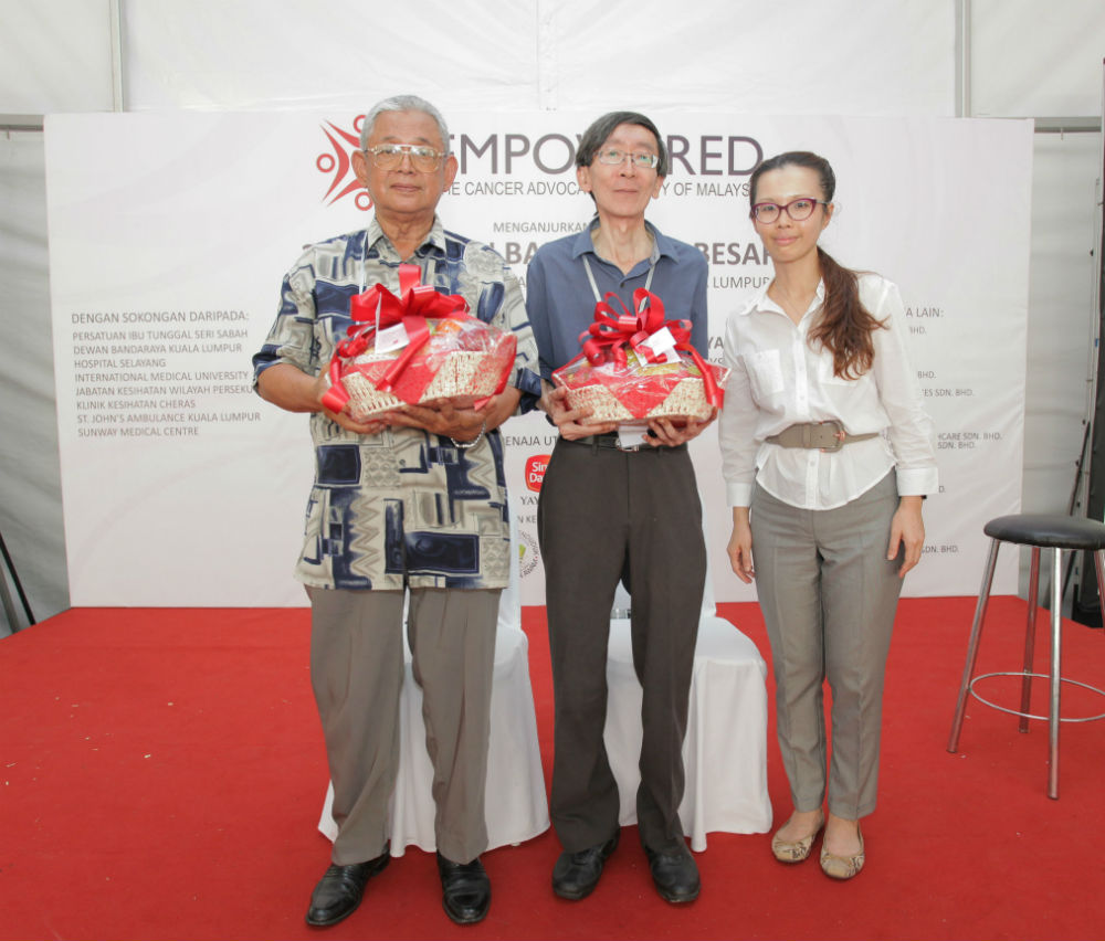 Tuan Haji Zainduddin Mohd Tahir and Mr. Yap receiving tokens of appreciation from Dr. Christina Ng